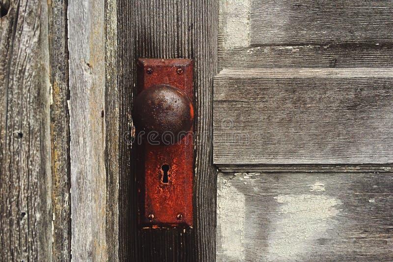 Rusty door knob on wooden door royalty free stock photo