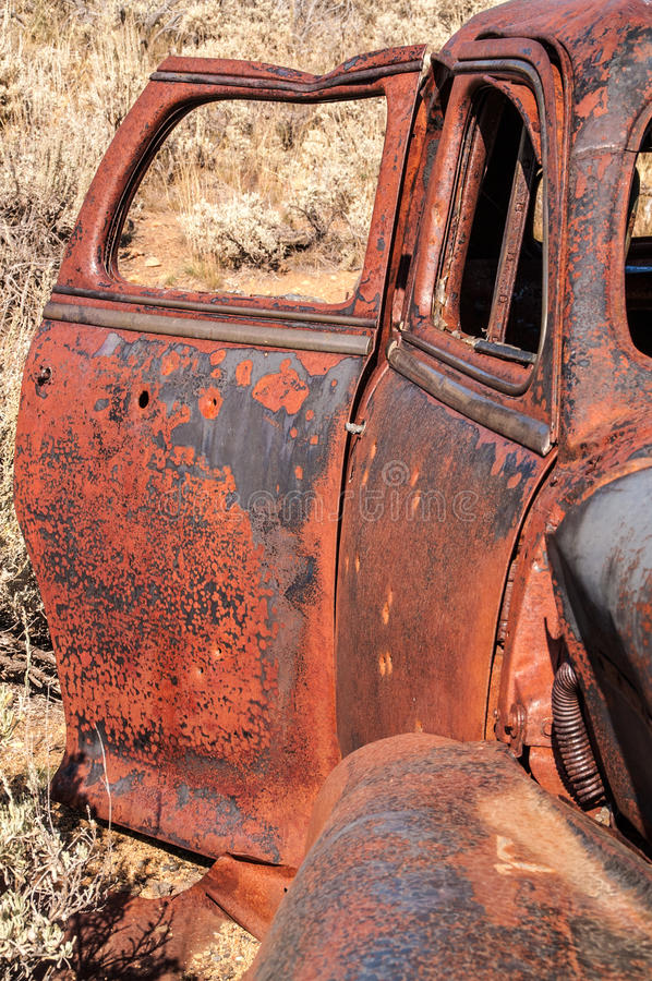 Rusty Doors. With just a bit of glass left in the rear door window and bullet holes here and there on this vintage vehicle stock image