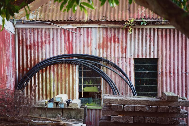 Rusty And Faded Old Country Storage Shack. Abandoned old country shack with faded paintwork on corrugated iron walls and roof, with assorted hunk piled in front stock photography