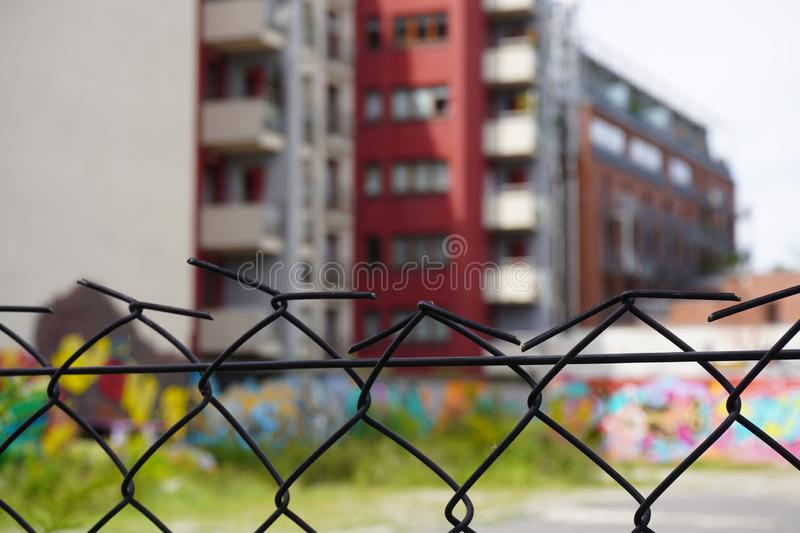 Rusty fence of mesh netting on the background of blurred modern house, the contrast of time. use of old and new materials royalty free stock photo