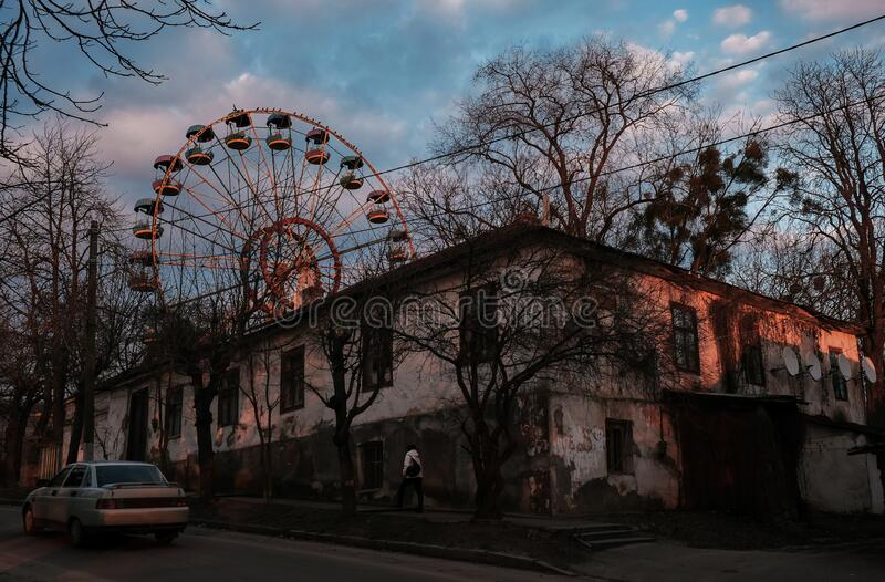 Rusty giant wheel in area with old houses at sunset stock photography