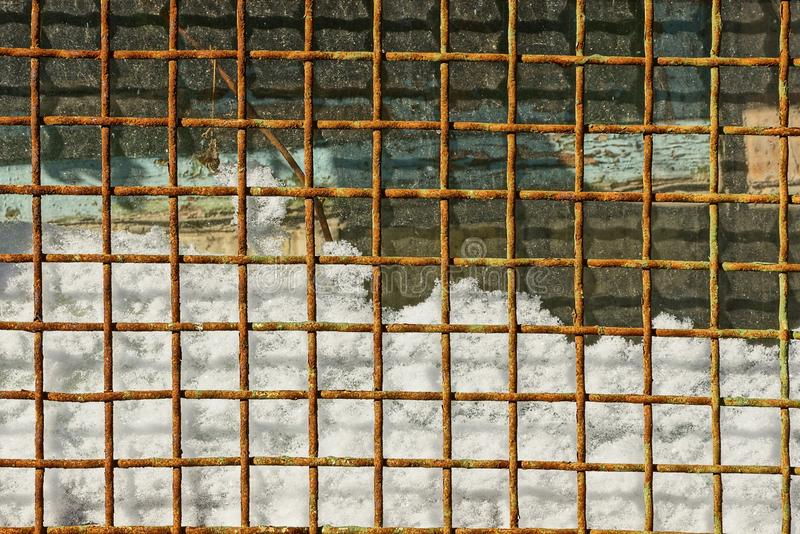 Rusty grating in the snow and glass windows royalty free stock photos