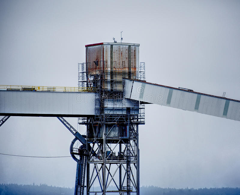 A rusty, grungy silo at a wharf against a gray sky. Taken in Seattle, Washington. The silo is old and corroded and is reflective of urban decay, industry, rust royalty free stock photos