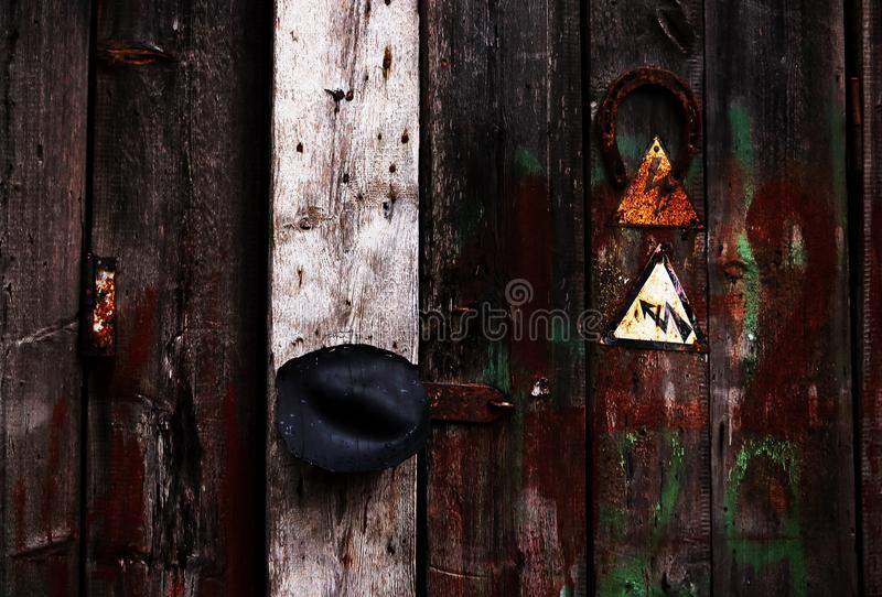 Rusty horse shoe and electricity alert signs on wooden plank door royalty free stock image