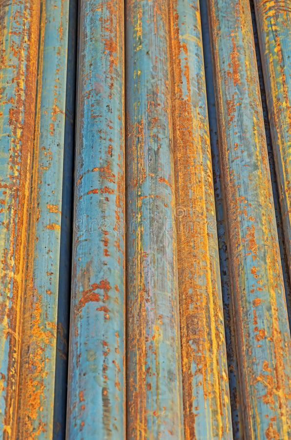 Rusty round steel bars. The rusty hot-rolled round steel bars in packs at the warehouse of metal products piled in the open air royalty free stock image