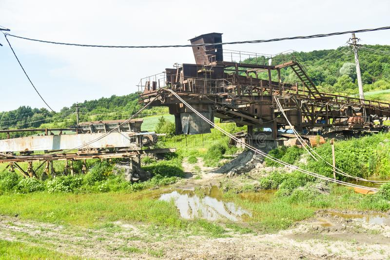 Rusty huge machines in abandoned coal mine. Heavy industry decay in Romania stock photography