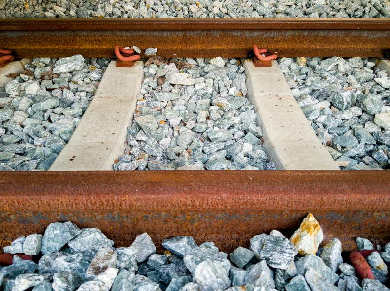 Rusty inactive railroad with concrete sleepers and rocks foundation. Inactive railroad covered with red rust lay down on the concrete sleepers and rocks royalty free stock photography