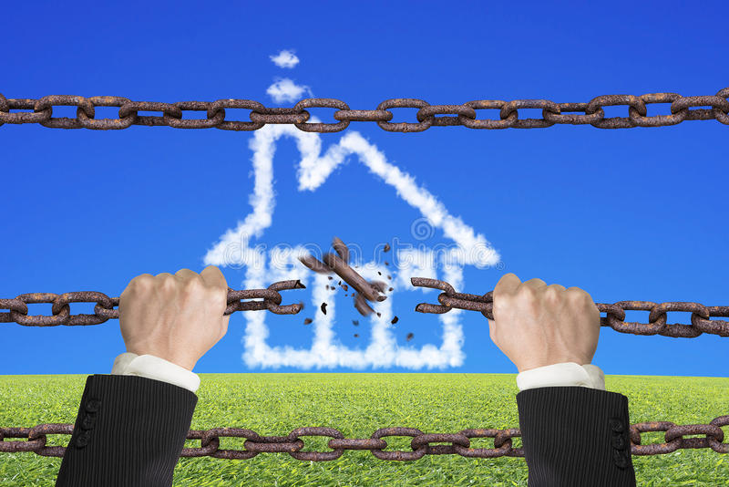 Rusty iron chains broken off by hands with house clouds. Rusty iron chains broken off by hands with house shape white clouds on sky grass background royalty free stock photography