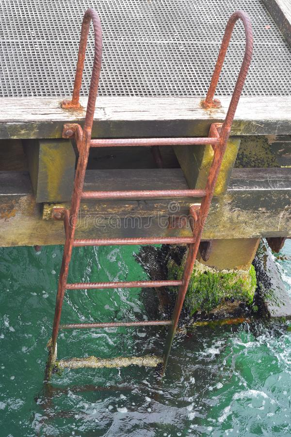 Rusty iron ladder on pier stock photography