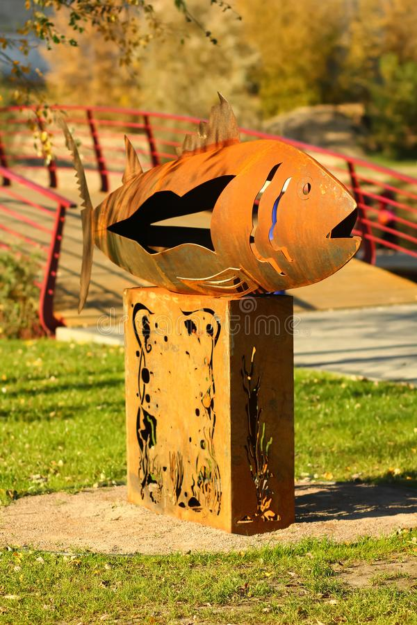 Rusty iron monument to a fish on the city riverfront / promenade stock photography
