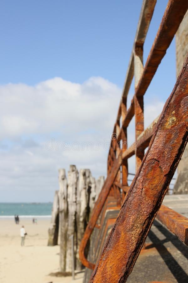Rusty iron railings in sunshine in St Malo France. Beach and wooden stakes in background stock images