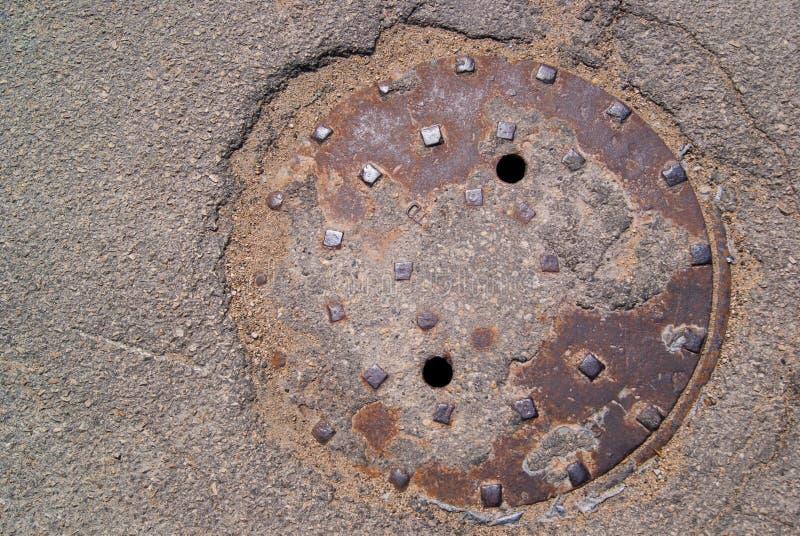 Rusty Manhole in het gat dat van de wegmens wordt geplaatst stock foto's