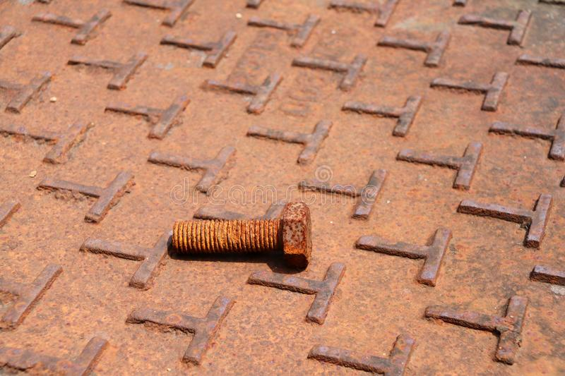 Rusty metal bolt Lay down on the steel plate floor in brown color with rusty iron. Rust is a reddish or yellowish-brown flaky coating of iron oxide that is stock photos