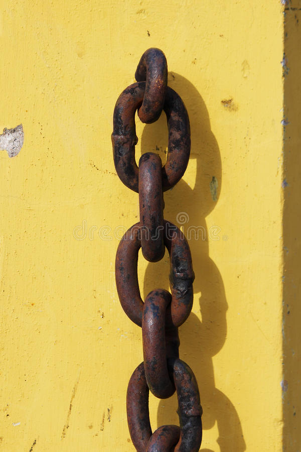 rusty metal chain hanging on yellow concrete pedestal and casts a shadow. stock photos