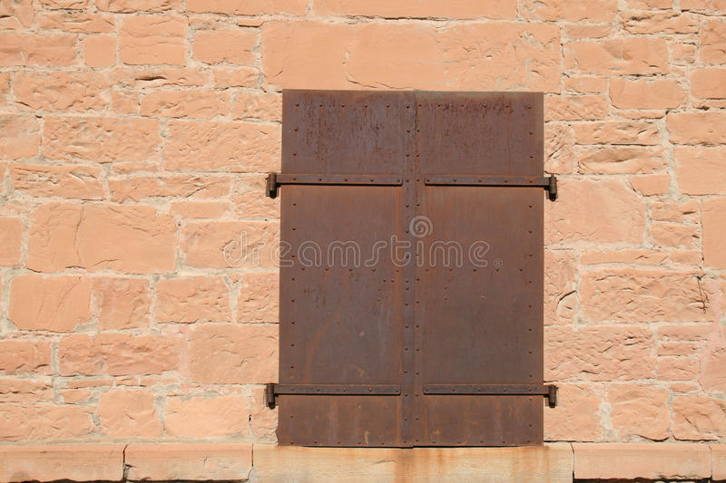 Rusty metal doors. In red sandstone wall stock image
