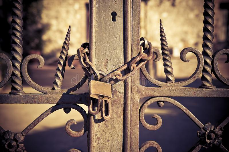 Rusty metal gate closed with padlock - concept image stock image