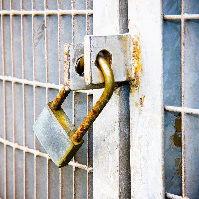 Rusty metal gate closed with padlock - concept image stock images