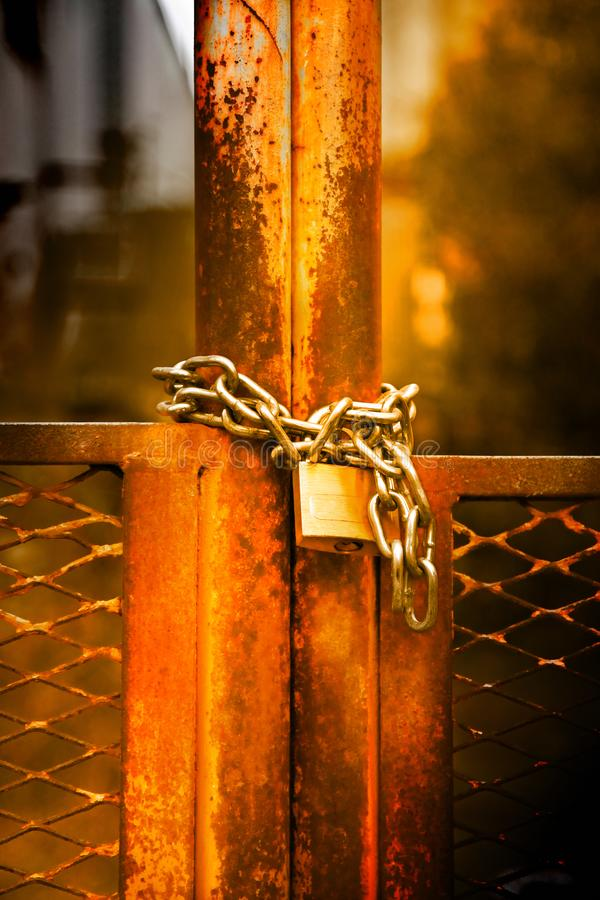 Rusty metal gate closed with padlock - concept image royalty free stock photo