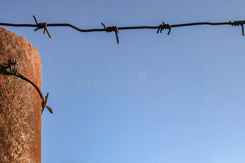 Rusty metal pole wrapped in barbed wire against blue sky. Close-up. Copy space royalty free stock image