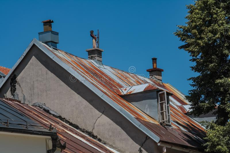 Rusty metal roof and a man figure on the chimney royalty free stock photography