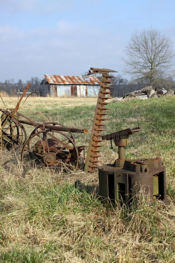 Rusty metal shed, Alabama. Rusty metal shed in Alabama, rusted farm tools, plow , planks, brown, tan stock image