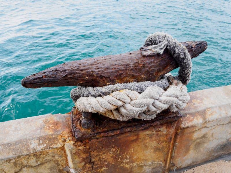 Rusty Mooring Bollard com corda no cais imagem de stock