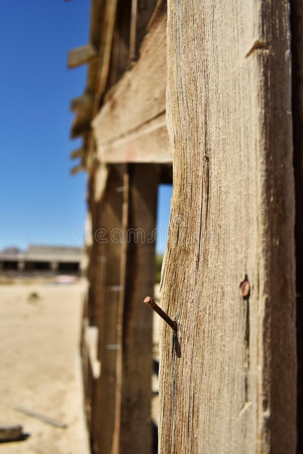 Nail in wood close up. Ruined building in the desert. Rusty nail in wood close up. Ruined building in the desert stock images
