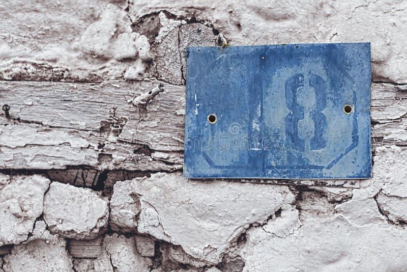 Rusty Number Sign 18 Blauw op Oud Wit Huis stock foto's