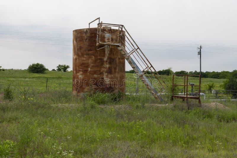 Rusty oil storage tank in a rural farm field royalty free stock photo