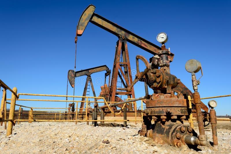 Rusty Oilfield Pumpjack som vaggar hästen över en wellhead Klart b arkivfoton