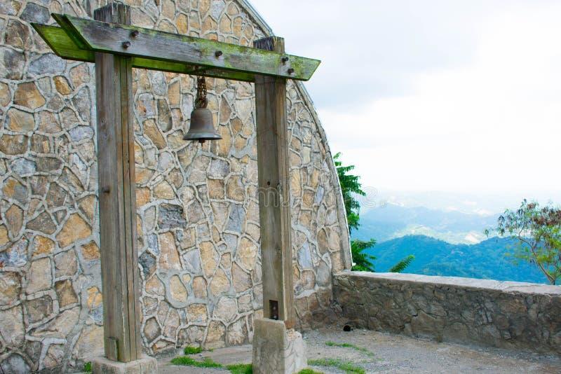 Rusty Old Bell Hanged na coluna de madeira musgoso com fundo de pedra da parede do arco do teste padrão, Overviewing na parte sup imagens de stock