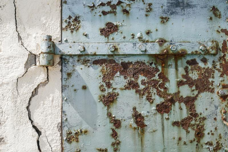 Rusty old blue door with cracked wall, abstract and textured background royalty free stock image