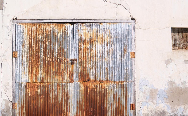 Rusty old corrugated iron doors on an storage building. Rusty weathered old corrugated iron doors with padlock on a grungy old building background stock image