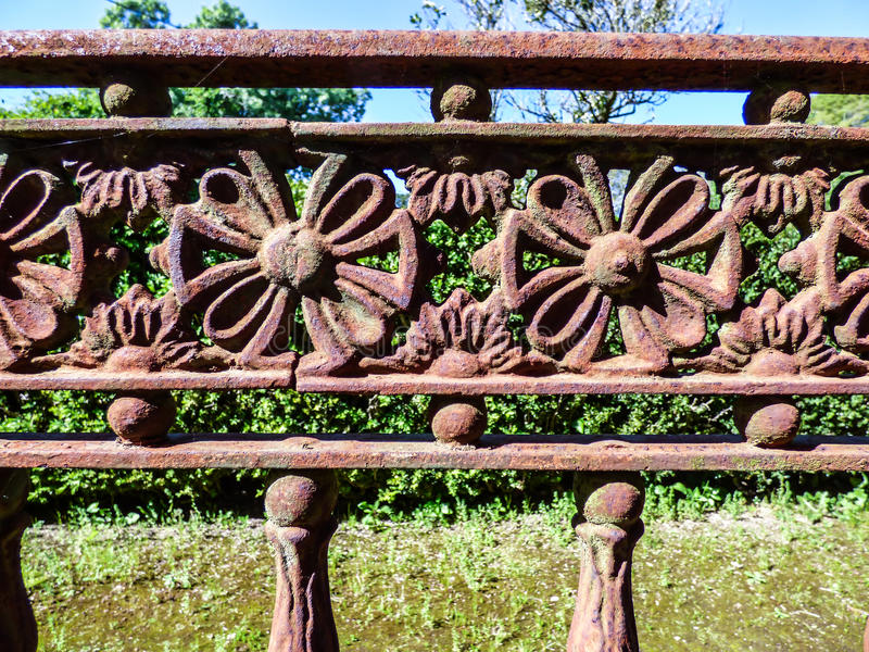 Rusty old iron fence with flower details royalty free stock photography
