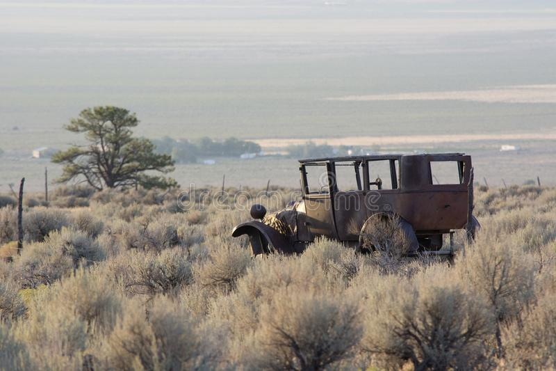 Rusty Old Jalopy Overlooking Sagebrush- und Pinyon-Kiefern-Wüste in Nevada lizenzfreie stockfotos