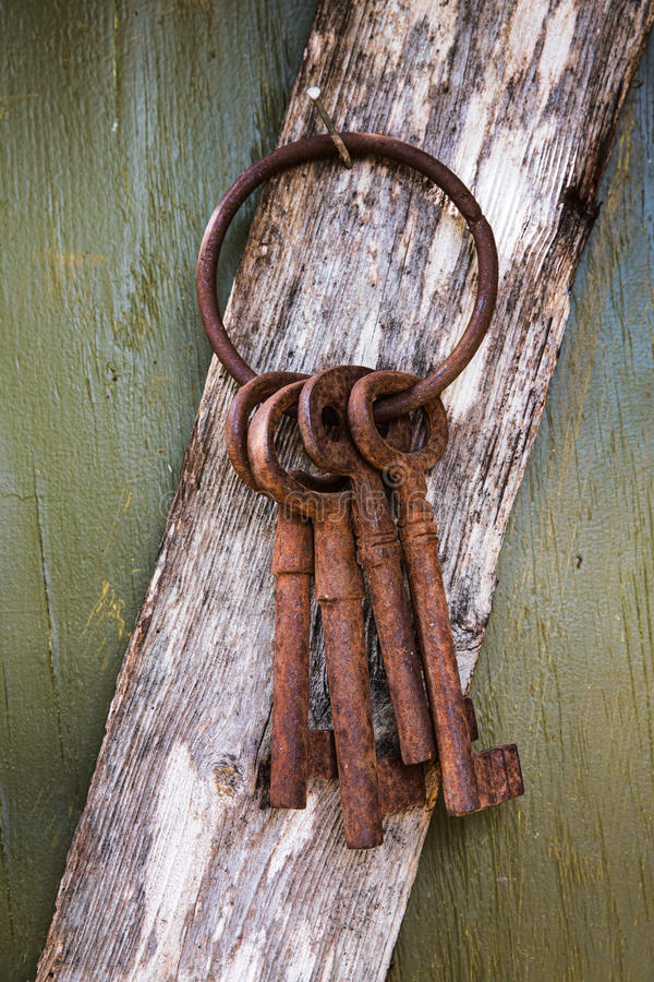 Rusty Old Keys Hanging from a Nail. Close-up shot of four rusty old keys hanging from a nail on a weathered board iagainst a green background n Austin, Texas stock photo