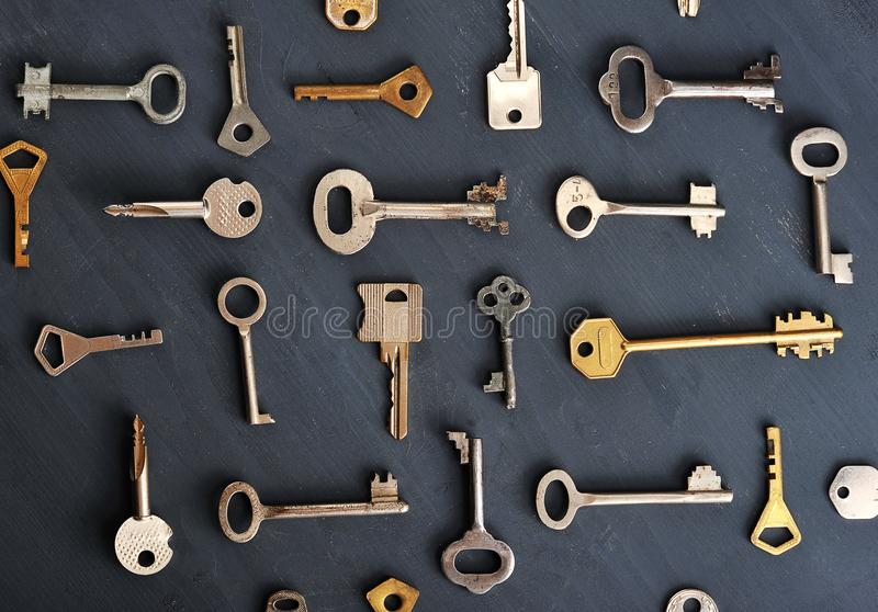 Rusty old keys locks - on dark wooden rustic background. Top view stock photo