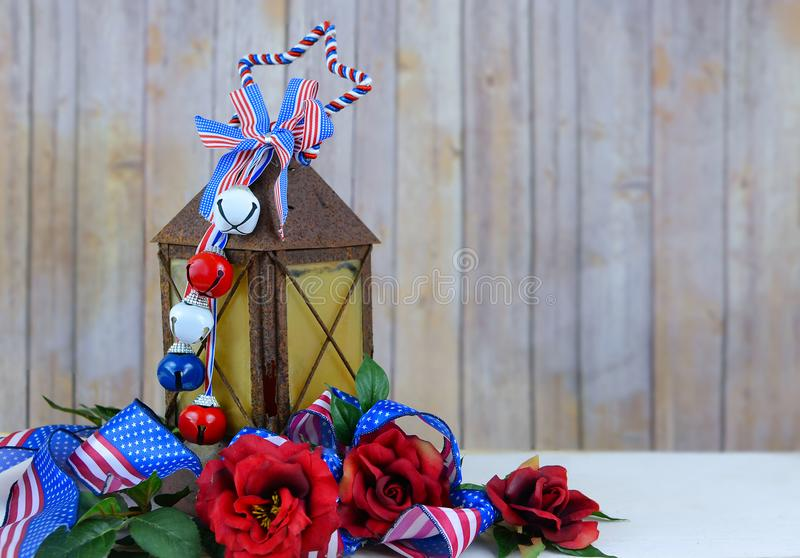 A rusty old lantern decorated with red, white and blue USA patriotic stars and stripes ribbons royalty free stock images