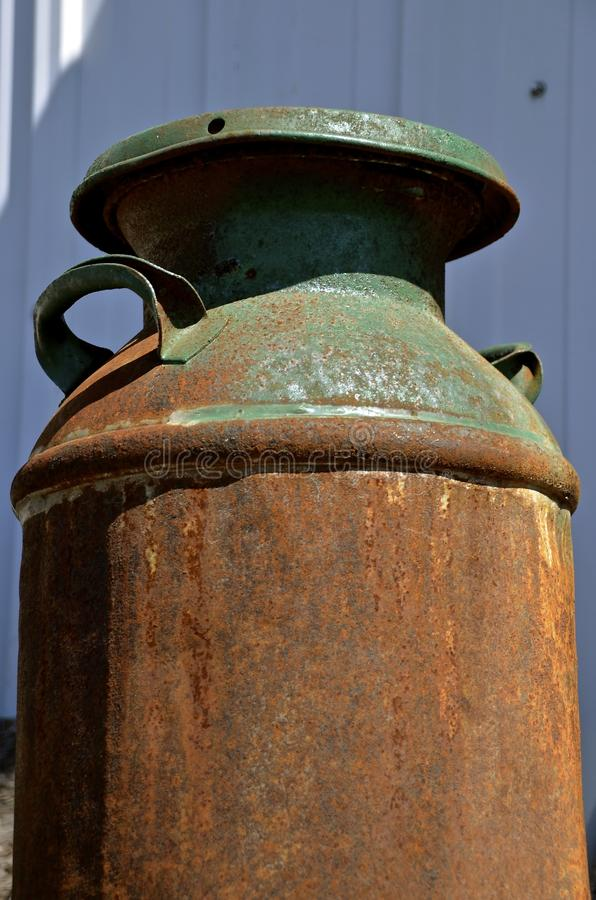Rusty old milk can once painted green stock image