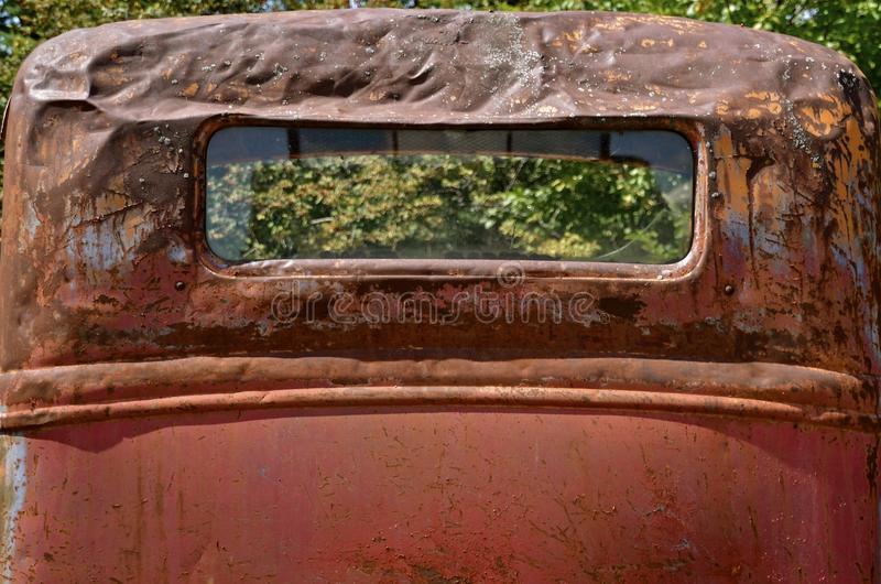 Rusty old pickup for salvage. A very old and rusty pickup has extensive cab damage royalty free stock images