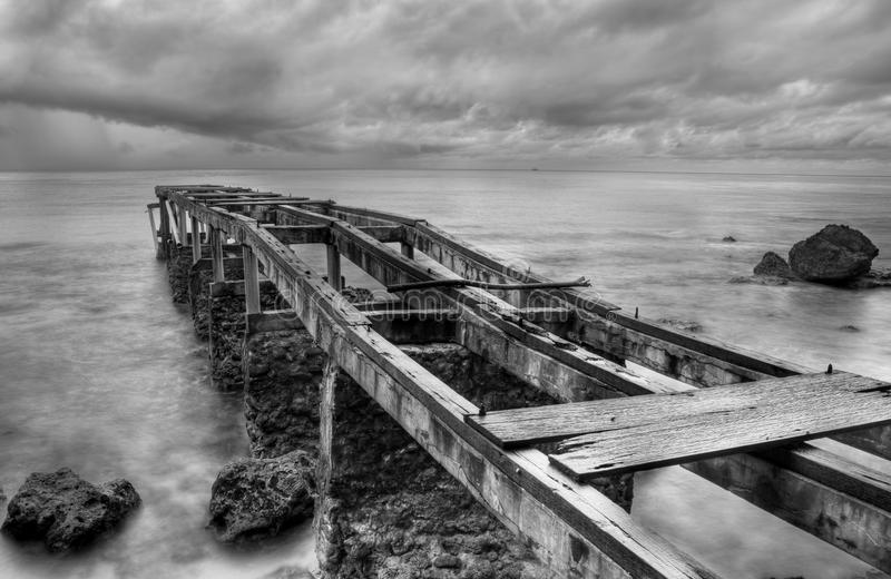 Rusty old pier in a cloudy day stock image