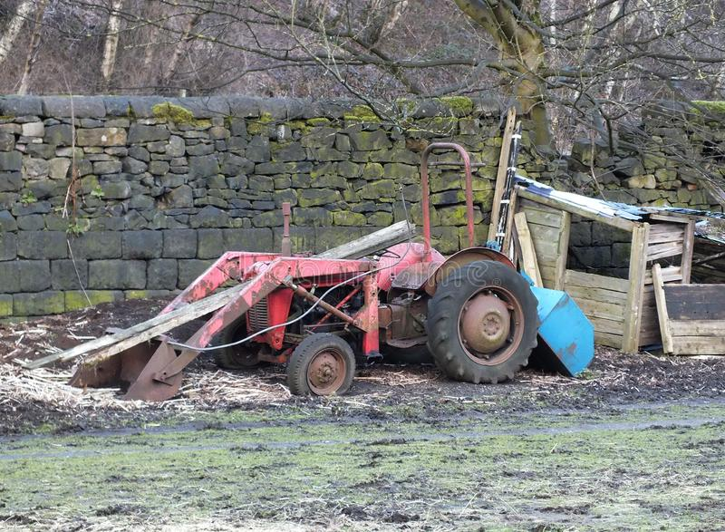 A rusty old red abandoned tractor next to a collapsing derelict wooden shed against a stone wall in a field stock images