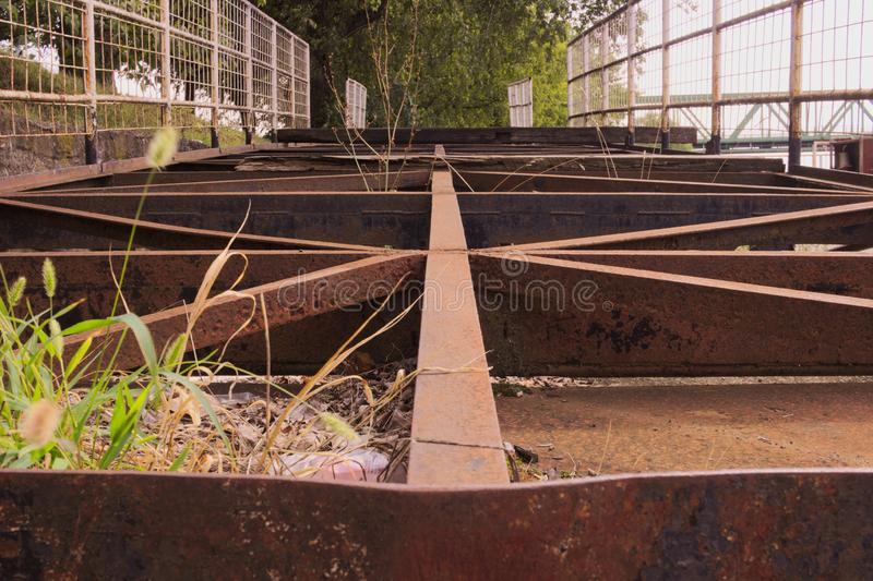 Rusty old steel structure lying on the ground. A rusty old steel structure is lying on the ground amongst weeds. Some of its steel beams are pointing towards stock images
