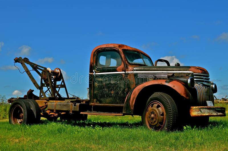 Rusty Old Tow Truck. A rusty old tow truck with a winch and patina is parked in the grass stock photos