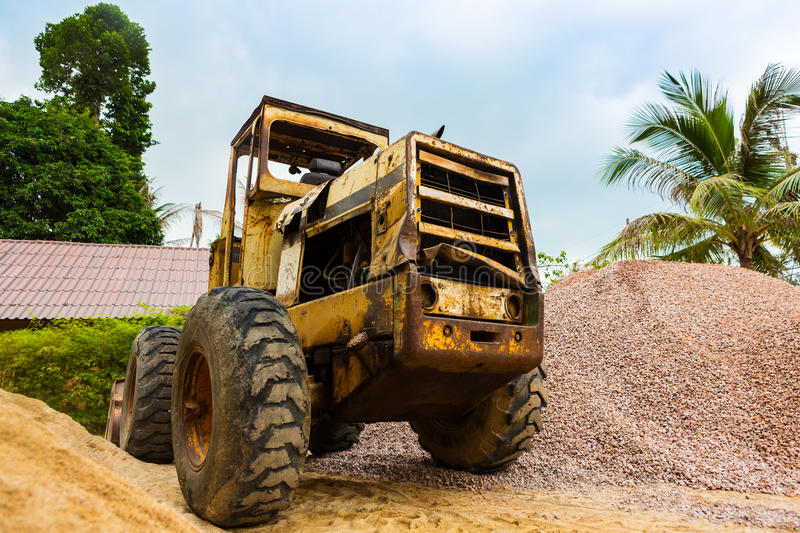 Rusty old tractor cute retired. Old truck helper stands near the pile of rubble in the tropical areas stock image
