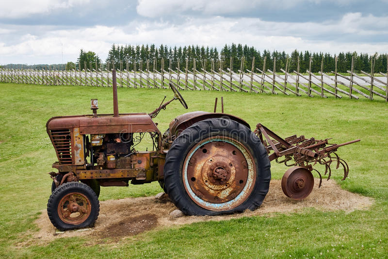 Rusty old tractor standing on the field. Rusty old tractor standing unused on the field royalty free stock image