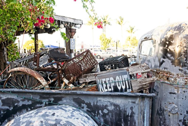 A rusty old truck with the bed filled with junk sits outside an establishment in Key, West Florida USA royalty free stock image