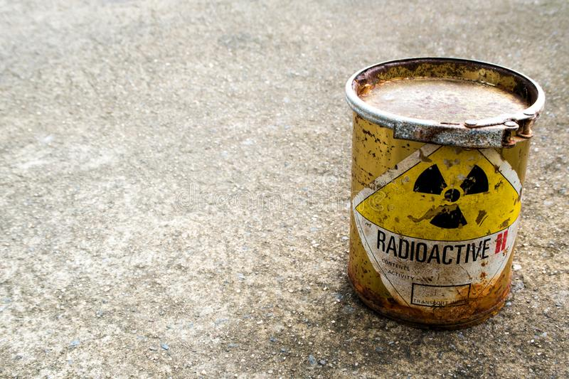 Rusty package of radioactive material container on the rough concrete floor. Radiation warning sign on rusty package of radioactive material container on the stock photos
