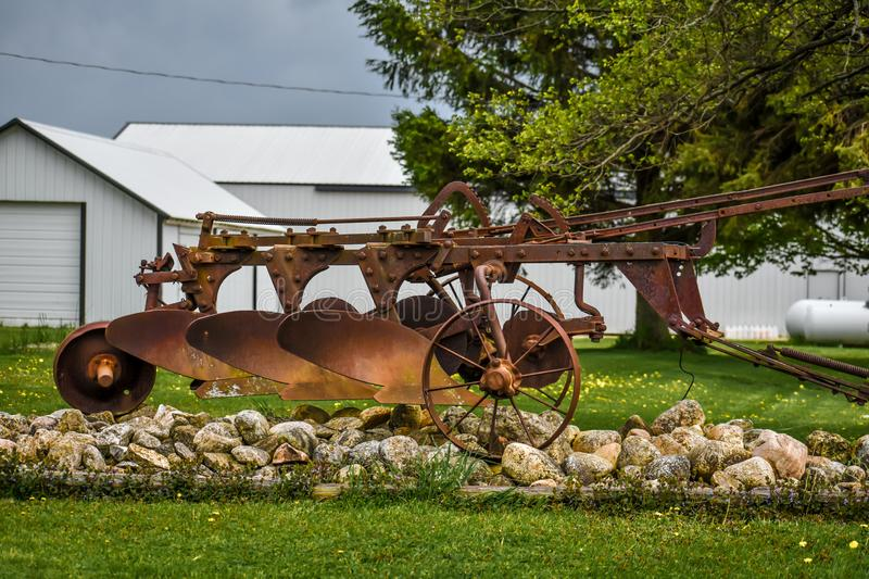 Antique Farm Equipment Displayed in Yard. A rusty piece of antique farm equipment used in plowing the fields on a farm in Wisconsin stock images