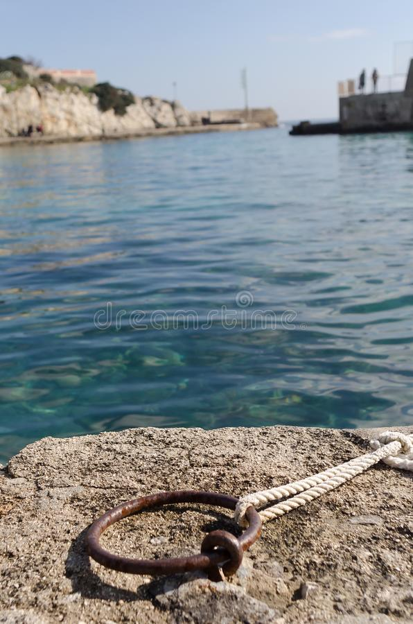 Rusty pier ring with a rope stock photography